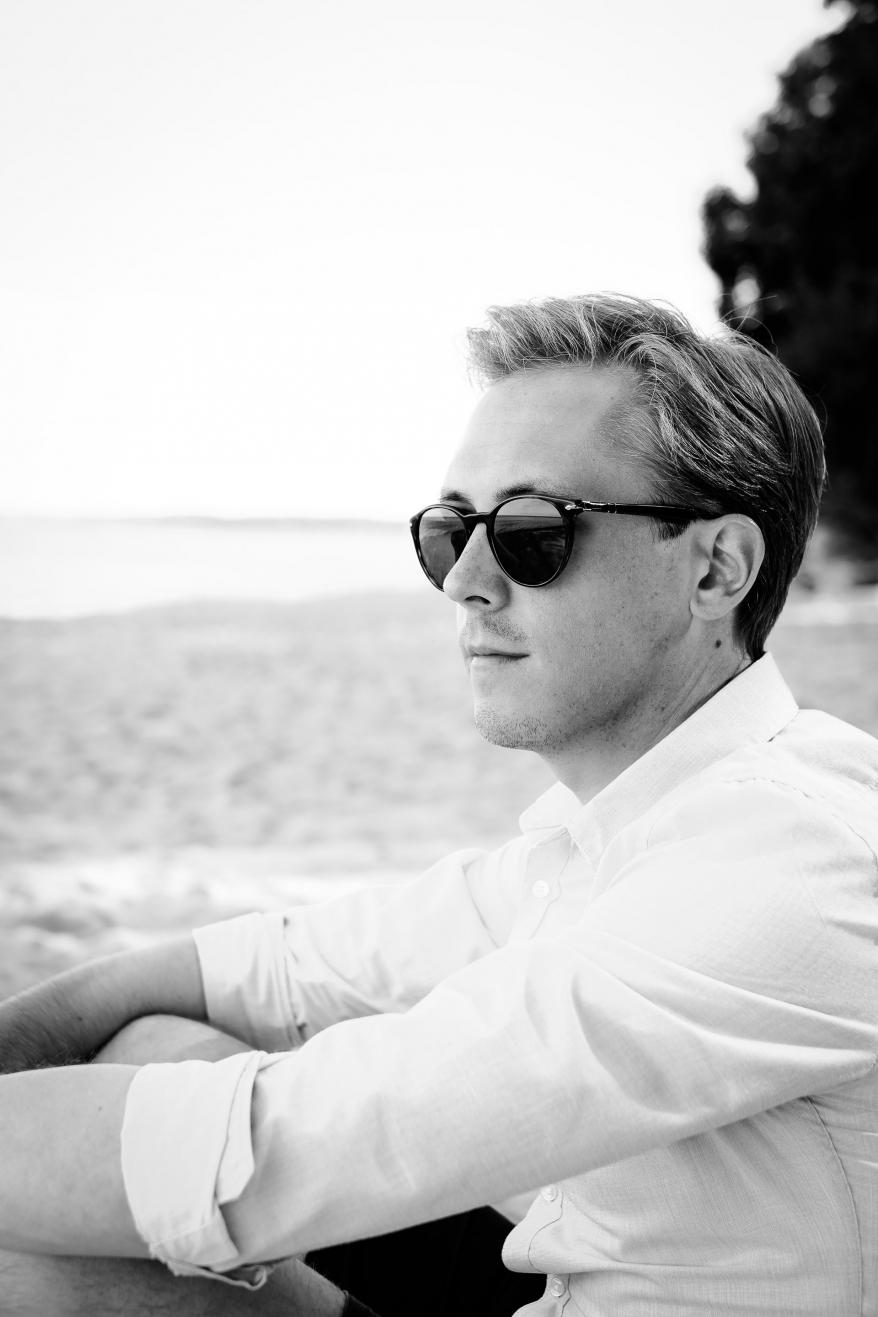 Man sitter på strand och tittar ut över havet. Foto.