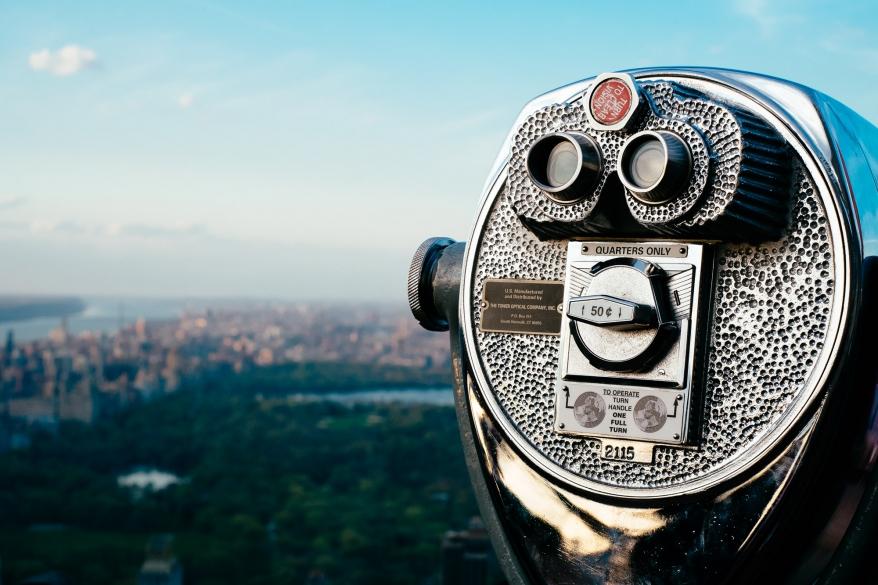 Kikare och utsikt över park. Foto.