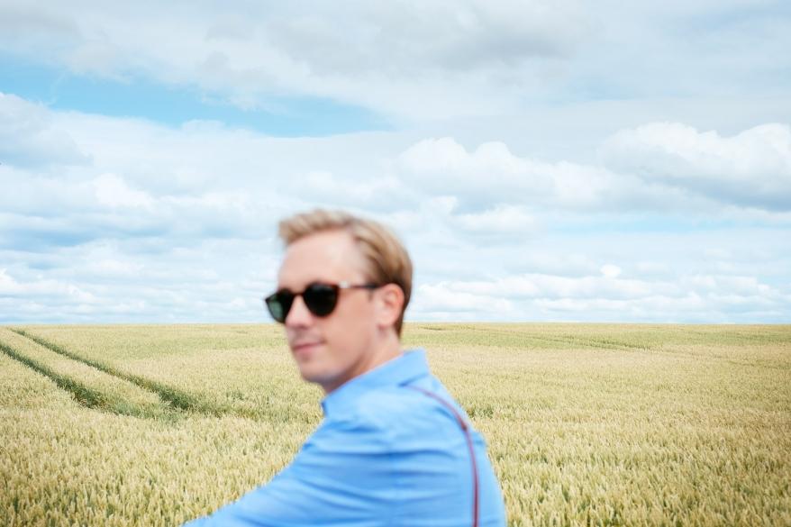Man med fält i bakgrunden. Foto.