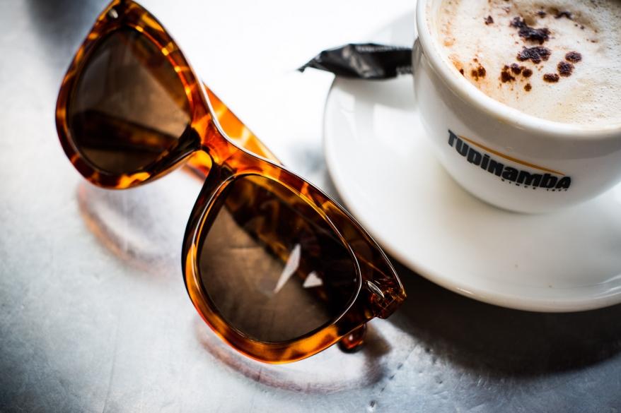 Solglasögon och en kopp kaffe. Foto.