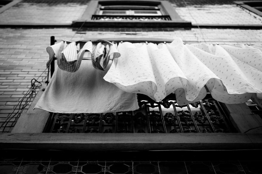 Tvätt som hänger utanför ett fönster. Foto.