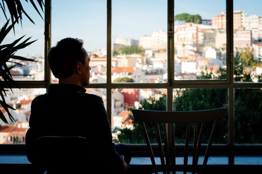 M in café with view of Lisbon