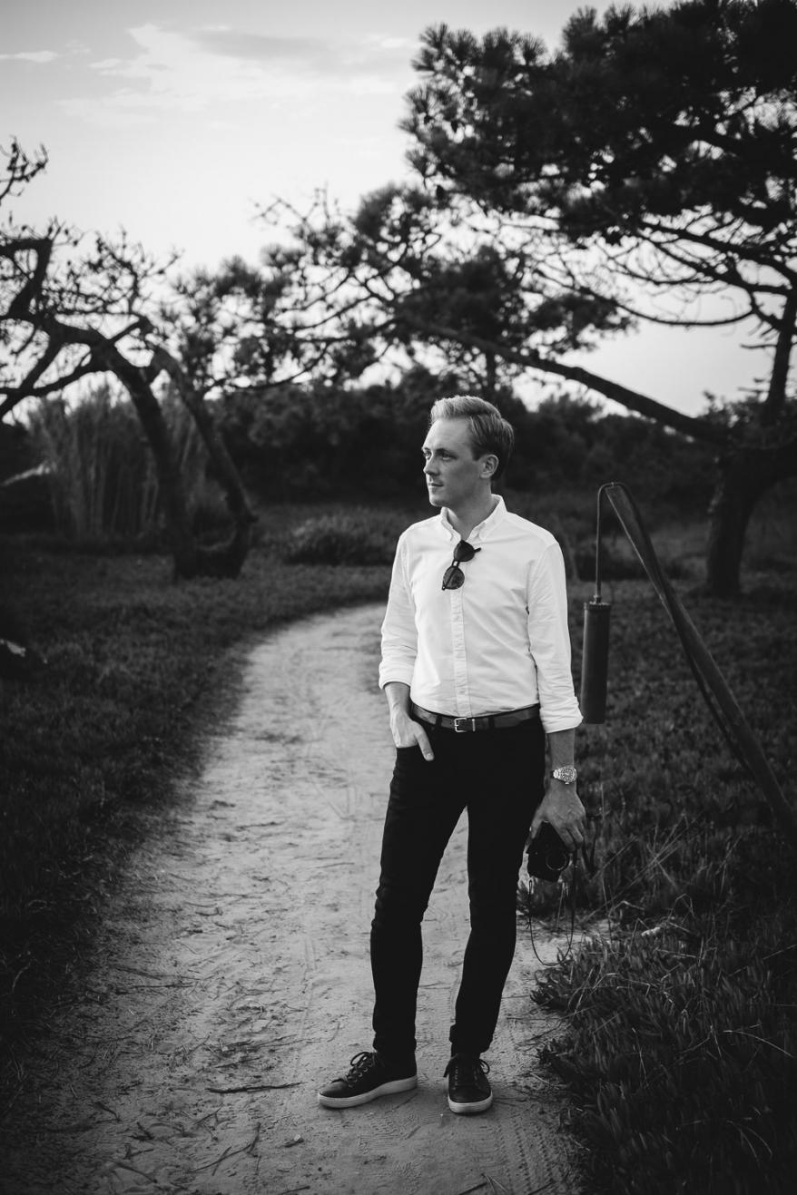 Man står på stig, i bakgrunden träd. Foto.