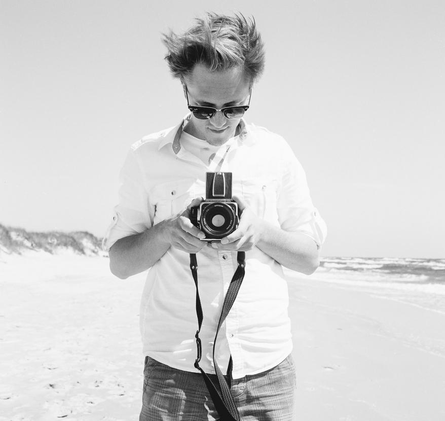 Man med kamera på stranden. Foto.