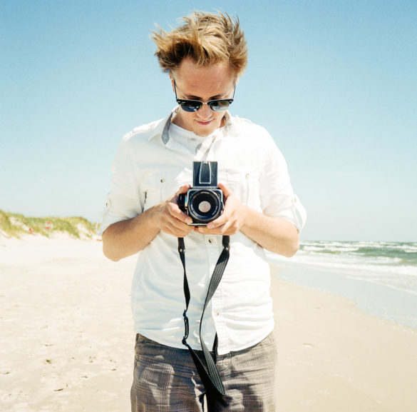 Man with camera on the beach. Photographer: Helena Bergqvist.
