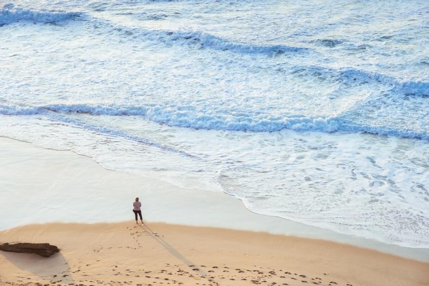 Kvinna står nere på stranden och tittar ut över havet. Foto.