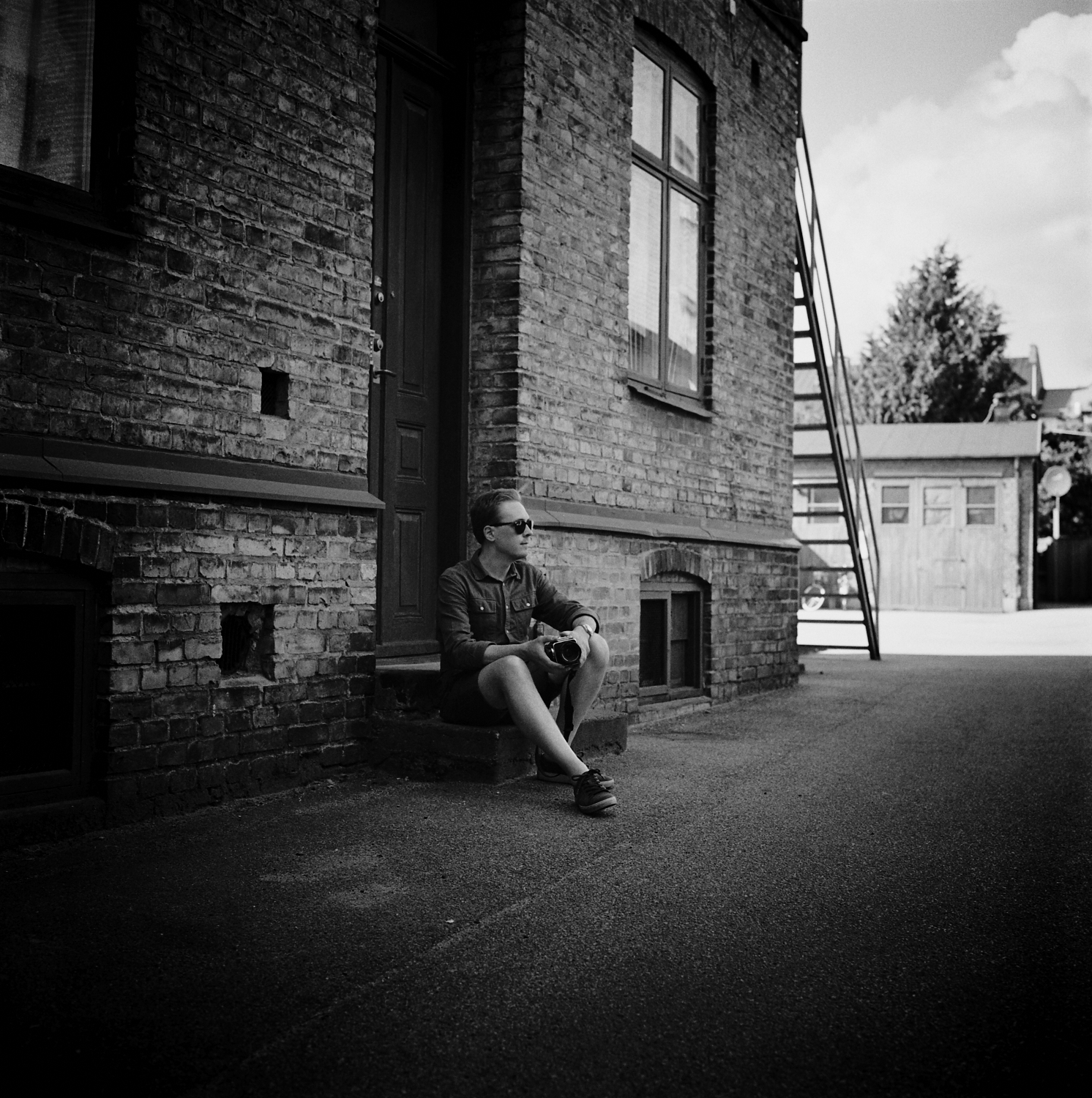 Man sitting on stairs in front of building. Photographer: Helena Bergqvist.