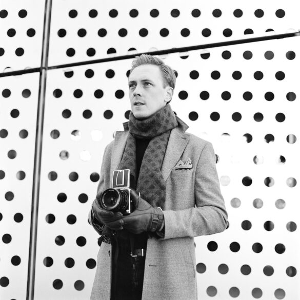 Man with an old camera standing in front of a wall with holes in it. Photographer: Helena Bergqvist.
