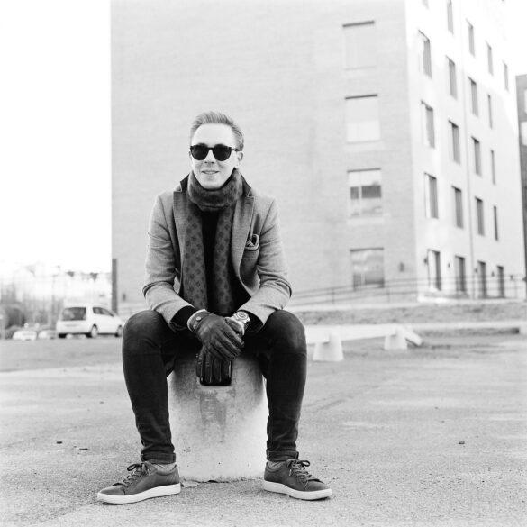 Man sitting on a concrete block in a parking lot. Photographer: Helena Bergqvist.