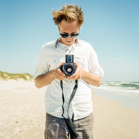 Man standing on the beach with an old camera. Photographer: Helena Bergqvist.
